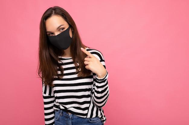 Aufnahme einer jungen attraktiven frau, die eine medizinische gesichtsmaske trägt, die über dem hintergrundwandschutz isoliert ist