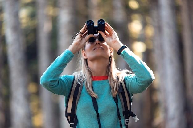 Aufnahme einer jungen frau des wanderers, die vögel durch ein fernglas-teleskop im wald sucht.
