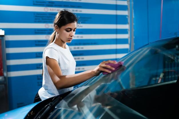 Aufnahme einer jungen frau, die ihr auto putzt