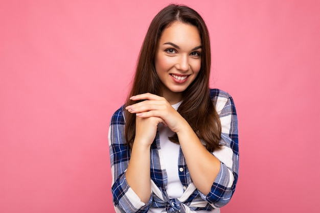 Aufnahme einer jungen positiven, bezaubernden, sexy lächelnden hübschen brünetten dame mit aufrichtigen emotionen, die ein trendiges karohemd einzeln auf rosafarbenem hintergrund mit leerem raum trägt