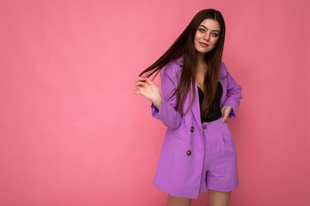 Aufnahme einer jungen positiven, glücklichen, attraktiven brünetten frau, die einen stylischen violetten anzug trägt, einzeln auf rosafarbenem hintergrund mit leerem raum. unternehmenskonzept.