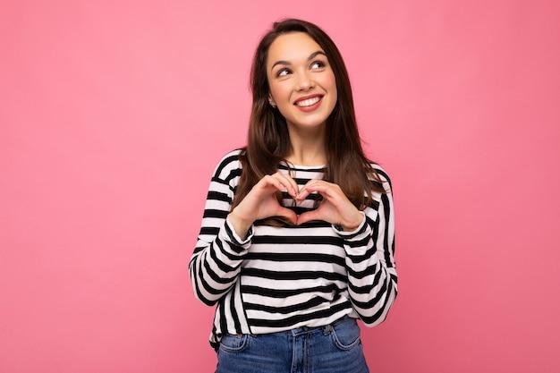 Aufnahme einer jungen positiven, glücklichen, netten, süßen brünetten frau mit aufrichtigen emotionen, die lässig gestreift trägt