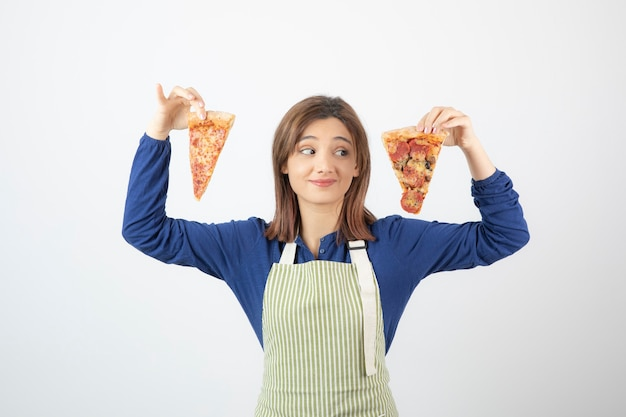 Aufnahme einer köchin in schürze, die pizzastücke auf weiß anschaut