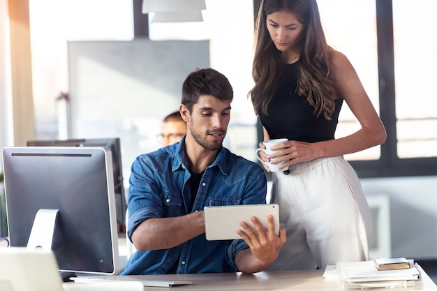 Aufnahme einer konzentrierten jungen frau, die neben ihrem kollegen steht und auf etwas auf einem digitalen tablet zeigt, während sie im büro zusammenarbeitet.