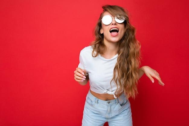 Aufnahme einer schönen, amüsanten, fröhlichen, jungen, dunkelblonden, lockigen frau, die über einer roten hintergrundwand isoliert ist und ein lässiges weißes t-shirt und eine stilvolle sonnenbrille mit blick auf die kamera trägt.