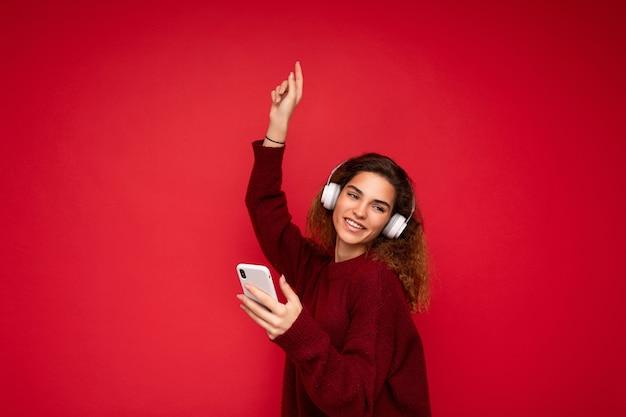 Aufnahme einer schönen jungen, brünetten, lockigen frau, die einen dunkelroten pullover trägt, isoliert auf rotem hintergrund