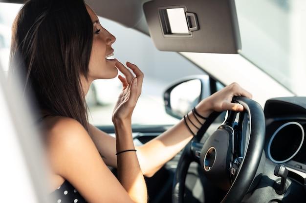 Aufnahme einer schönen jungen frau, die lippenbalsam aufträgt, während sie im rückspiegel im auto schaut.