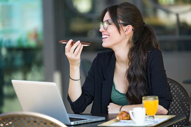 Aufnahme einer schönen jungen frau, die mit ihrem handy spricht und frühstückt, während sie mit ihrem laptop in einem café arbeitet.