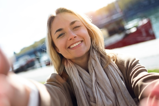 Aufnahme einer schönen jungen frau, die selfie mit smartphone in der stadtstraße macht.