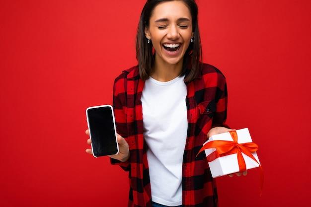 Aufnahme einer schönen, positiv lachenden jungen brünetten frau, die über einer roten hintergrundwand isoliert ist und ein weißes, lässiges t-shirt und ein rotes und schwarzes hemd trägt, das eine weiße geschenkbox mit rotem band und handy hält