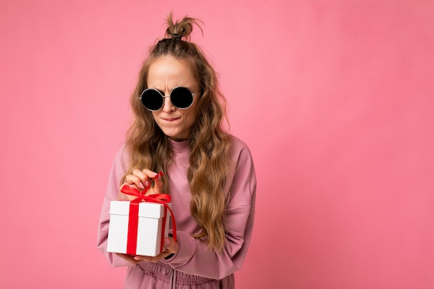 Aufnahme einer schönen positiven emotionalen jungen blonden lockigen frau, die über rosafarbener hintergrundwand isoliert ist und rosa sportkleidung und sonnenbrille trägt, die geschenkbox hält und überraschung auspackt