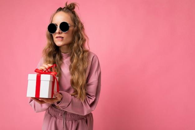 Aufnahme einer schönen positiven jungen blonden lockigen frau, die über rosafarbener hintergrundwand isoliert ist und rosa sportkleidung und sonnenbrille trägt, die geschenkbox hält und überraschung auspackt, die zur seite schaut. freiraum