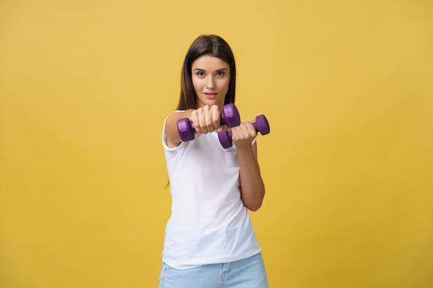 Aufnahme einer schönen und sportlichen jungen frau, die gewichte gegen gelben hintergrund hebt.