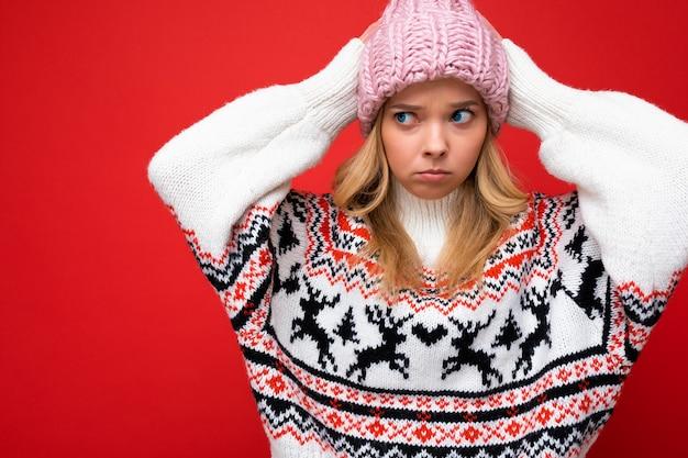 Aufnahme einer schönen verärgerten traurigen beleidigten jungen blonden frau, die über einer roten hintergrundwand isoliert ist und einen winterpullover und einen rosa hut trägt, der zur seite schaut.
