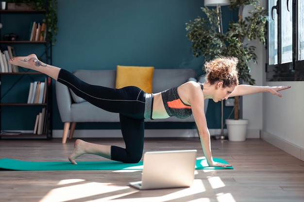 Aufnahme einer selbstbewussten, sportlichen jungen frau, die nach online-fitness-kursen über laptop auf dem boden in ihrem wohnzimmer zu hause hypopressive übungen macht.