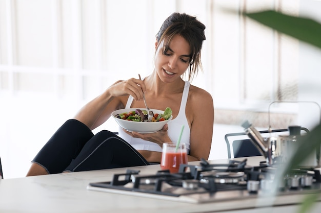 Aufnahme einer sportlichen jungen frau, die in der küche zu hause salat isst und fruchtsaft trinkt.