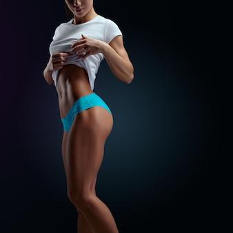 Aufnahme einer starken frau mit muskulösem bauch in sportkleidung. sinnliches junges weibliches modell, das auf schwarzem hintergrund aufwirft. schöne frau mit sauberer und leuchtender haut auf grauem hintergrund.
