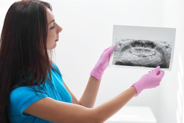 Aufnahme einer zahnärztin, die in ihrem büro arbeitet und einen röntgenscan eines radiologie-professionalitätsbehandlungs-arztberufs-wissenserfahrungskonzepts der kiefertechnologie untersucht.