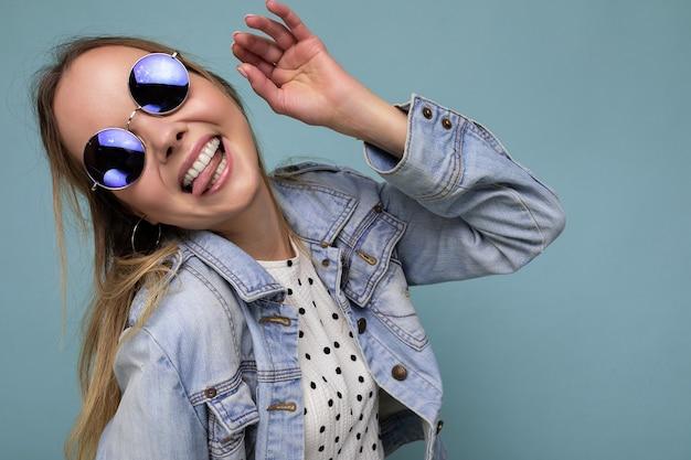 Aufnahme einer ziemlich positiven, amüsanten, lustigen jungen blonden frau, die eine blaue jeansjacke und eine stylische sonnenbrille trägt, isoliert über der blauen hintergrundwand, die zur seite schaut und die zunge zeigt.