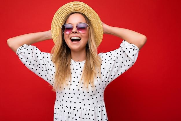 Aufnahme einer ziemlich positiven, fröhlichen jungen blonden frau mit sommerkleid-strohhut und stilvoller brille
