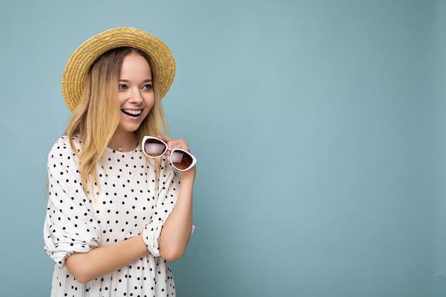 Aufnahme einer ziemlich positiven jungen blonden frau mit sommerkleid strohhut und stilvoller sonnenbrille einzeln auf blauer hintergrundwand mit blick auf die seite