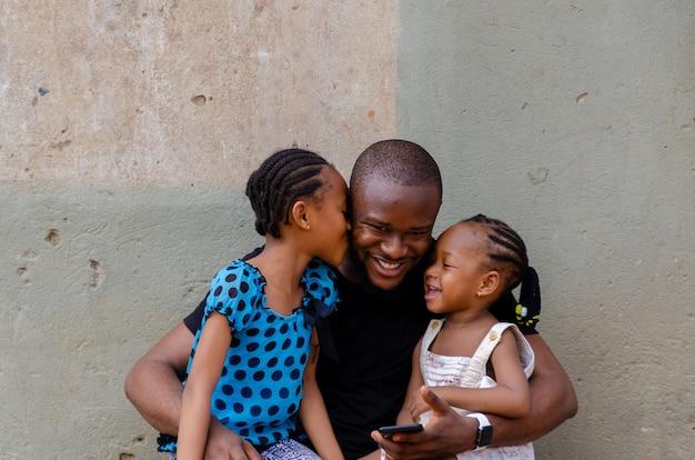Aufnahme eines afrikanischen vaters, der aufgeregt ist, während er sich mit seinen kindern verbindet