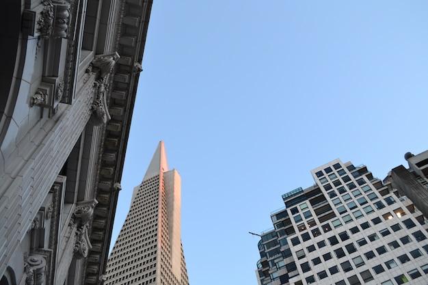 Aufnahme eines alten historischen gebäudes in der nähe zeitgenössischer abstrakter architektonischer hochhäuser