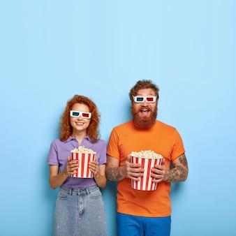 Aufnahme eines amüsierten glücklichen rothaarigen freundes und einer freundin, die im kino unterhalten werden, eine 3d-brille tragen, eine lustige komödie sehen, popcorn aus dem korb essen, freizeit miteinander verbringen, einen lustigen film genießen