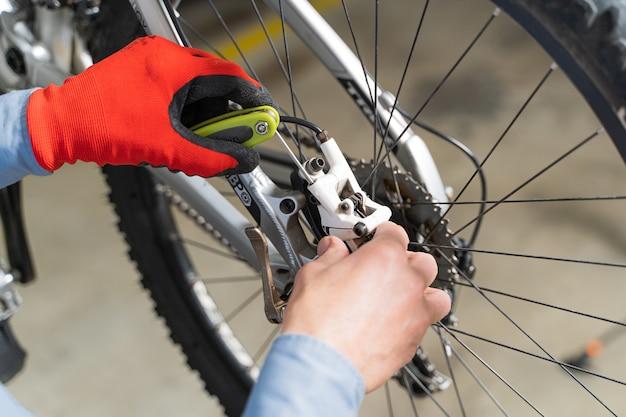 Aufnahme eines arbeitenden mechanikers, der ein fahrrad repariert