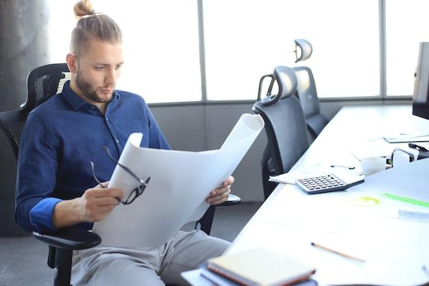 Aufnahme eines attraktiven männlichen architekten, der pläne hält, während er in seinem büro sitzt.