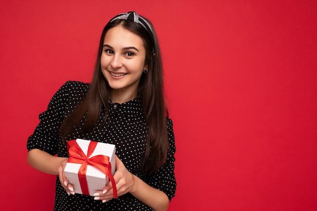 Aufnahme eines charmanten, glücklich lächelnden brünetten mädchens, das über einer roten hintergrundwand isoliert ist und eine schwarze bluse trägt, die eine weiße geschenkbox mit rotem band hält und in die kamera schaut. platz kopieren