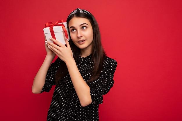 Aufnahme eines charmanten, glücklichen, nachdenklichen brünetten mädchens, das über einer roten hintergrundwand isoliert ist und eine schwarze bluse trägt, die eine weiße geschenkbox mit rotem band hält und nach oben schaut. freiraum