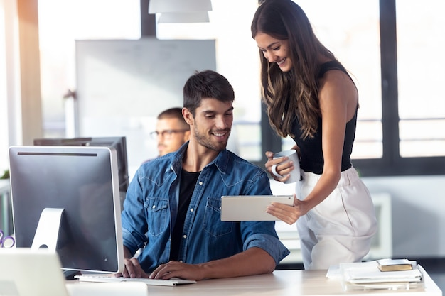 Aufnahme eines erfolgreichen jungen geschäftspaares, das im modernen startup-büro mit digitalem tablet zusammenarbeitet.