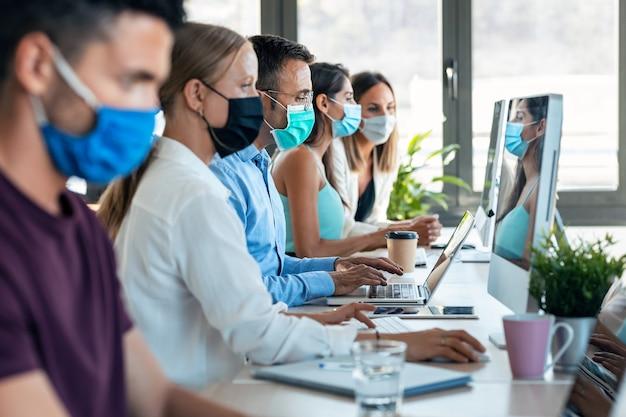 Aufnahme eines erfolgreichen konzentrierten geschäftsteams, das eine hygienische gesichtsmaske trägt, während es im büro zusammenarbeitet und sichere abstände am coworking-platz einhält.