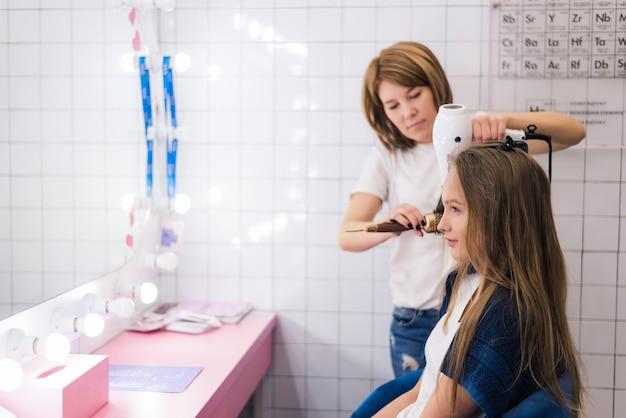 Aufnahme eines fröhlichen friseurs, der das haar einer schönen jungen frau föhnt, die in ihrem schönheitssalon arbeitet