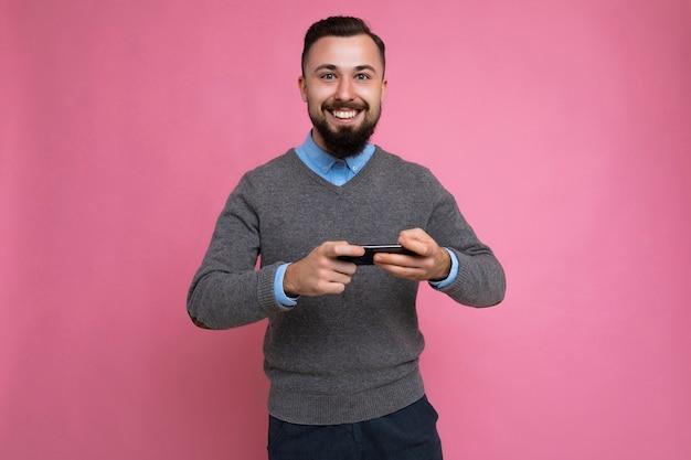 Aufnahme eines glücklichen, fröhlichen, gutaussehenden, unrasierten, brünetten mannes mit bart, der einen grauen pullover trägt