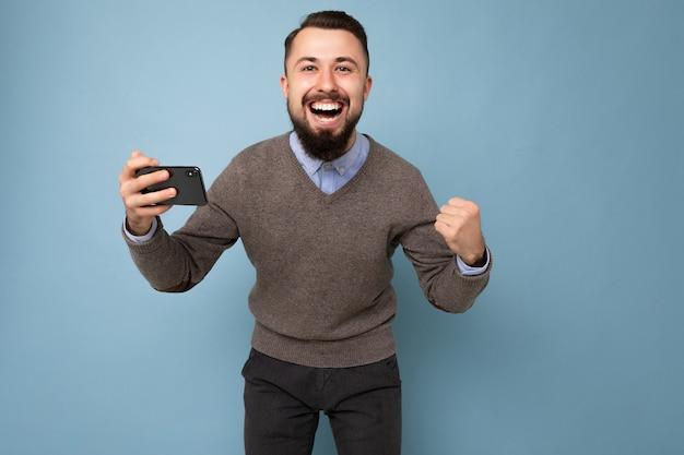 Aufnahme eines glücklichen, gutaussehenden jungen, brünetten, unrasierten mannes mit bart, der einen alltäglichen grauen pullover und ein blaues hemd trägt, isoliert auf der hintergrundwand, die das smartphone mit blick auf die kamera hält und spaß hat und ja schreit