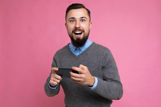 Aufnahme eines glücklichen, gutaussehenden, jungen, brünetten, unrasierten mannes mit bart, der jeden tag grauen pullover und blau trägt