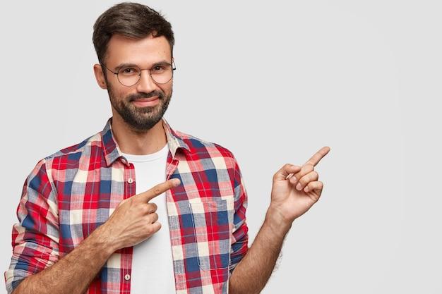 Aufnahme eines gut aussehenden mannes mit zufriedenem ausdruck, hat dunkle stoppeln, zeigt mit den vorderfingern zur seite