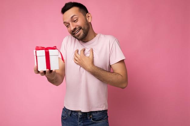 Aufnahme eines gutaussehenden, glücklich lächelnden, überraschten jungen mannes mit bart einzeln auf rosafarbener hintergrundwand, der ein rosa t-shirt trägt, das eine weiße geschenkbox mit rotem band hält und auf die gegenwart schaut