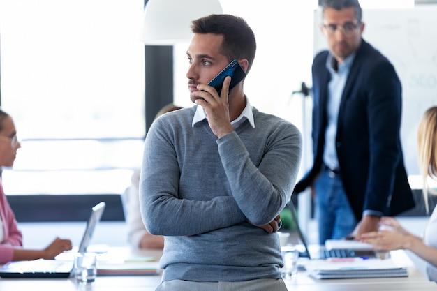 Aufnahme eines gutaussehenden jungen geschäftsmannes, der auf dem coworking space telefoniert.