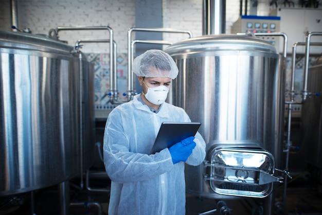Aufnahme eines hochkonzentrierten und fokussierten kaukasischen technologen, der die produktion in der lebensmittelverarbeitungsfabrik oder in der pharmazeutischen industrie kontrolliert