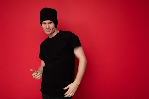 Aufnahme eines hübschen, glücklich lächelnden jungen mannes, der isoliert über einer roten hintergrundwand steht und ein schwarzes t-shirt für mockup und schwarzen hut trägt und in die kamera schaut. freier speicherplatz, kopienraum