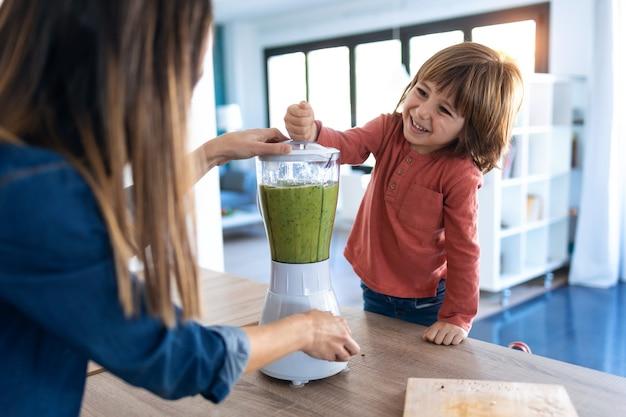 Aufnahme eines jungen, der seiner mutter hilft, einen entgiftungssaft mit einem mixer in der küche zu hause zuzubereiten.