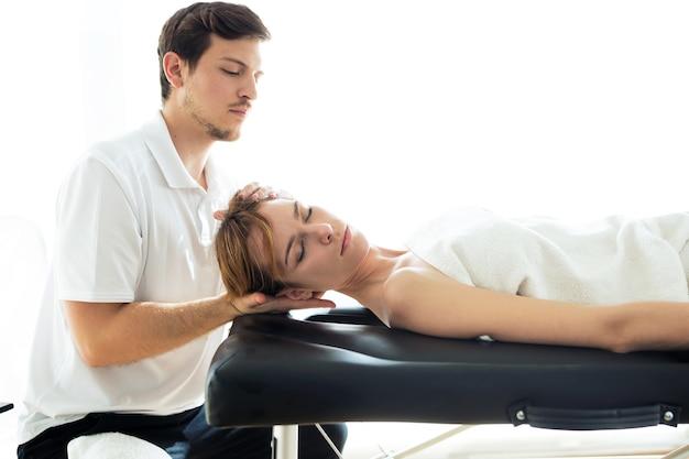 Aufnahme eines jungen physiotherapeuten, der dem patienten in einem physiotherapieraum eine nackenbehandlung durchführt. rehabilitation, medizinische massage und manuelles therapiekonzept.