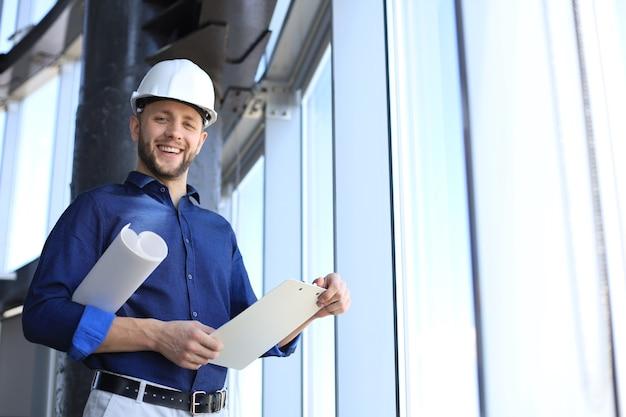 Aufnahme eines lächelnden männlichen architekten, der einen helm trägt und ein neues gebäude inspiziert.
