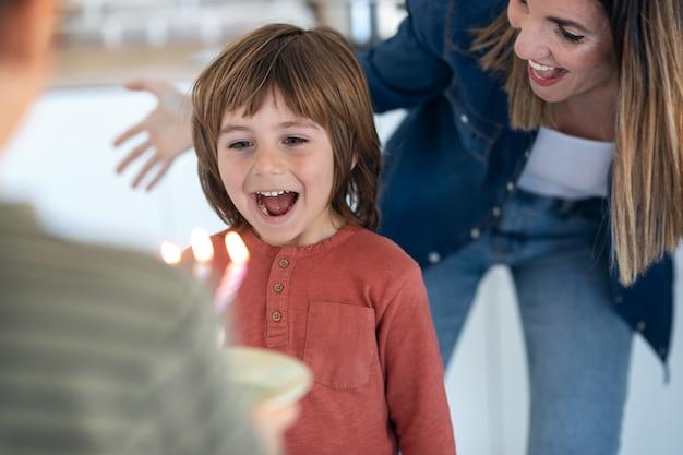 Aufnahme eines lustigen jungen überrascht und spaß mit geburtstagskuchen in der küche zu hause.
