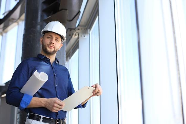 Aufnahme eines männlichen architekten, der einen helm trägt und ein neues gebäude inspiziert.