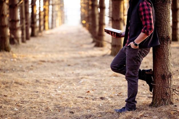 Aufnahme eines mannes, der ein buch hält und in einem wald posiert