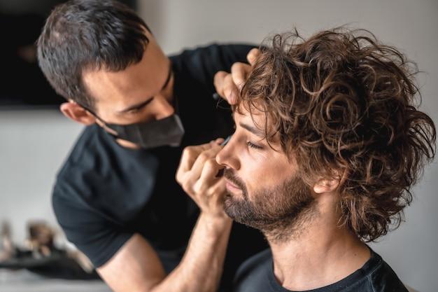 Aufnahme eines maskenbildners in einer medizinischen maske, der seinen job macht - neue normalität